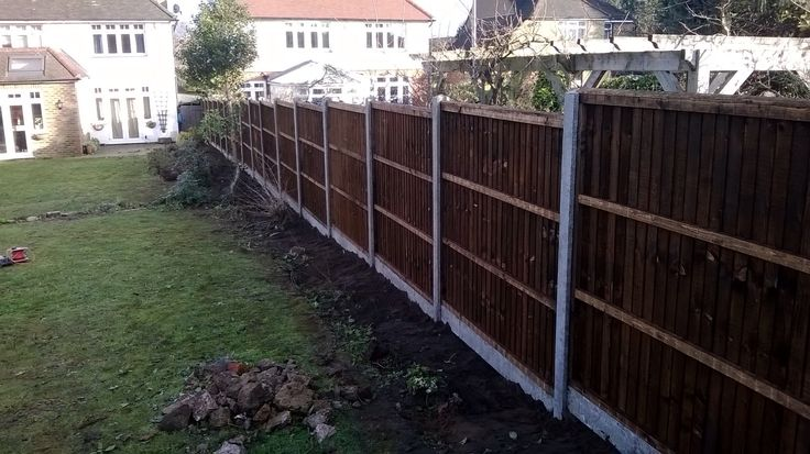 Concrete post and close board fence installed using laser
