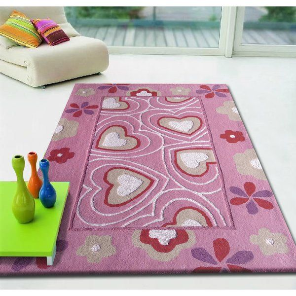A playful rug featuring whimsical heart motifs, Rug presents a pink background with hearts in red, white and purple. Perfect for babies, children or twins, this rug adds a spark of colour to any room.