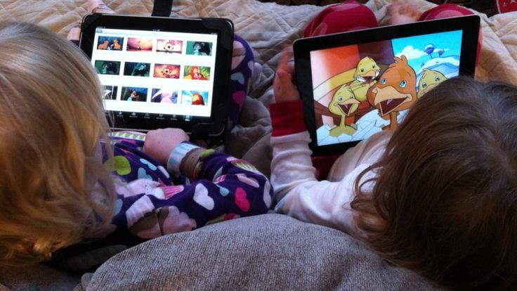 Foto uppifrån och bakifrån på två barn med varsin iPad i knät. Flickr cc-licens: Wayan Vota