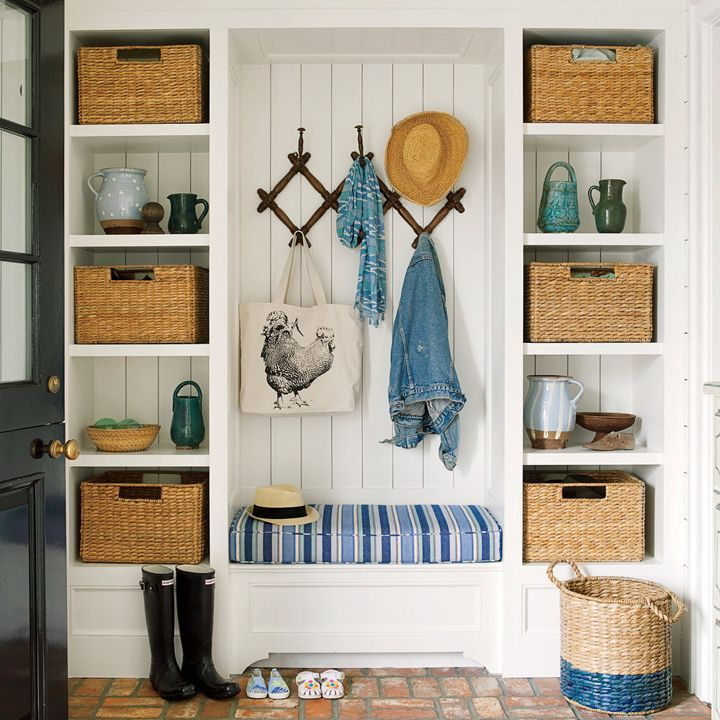 Love this organized mudroom with paneled walls, storage baskets, blue striped built in bench and lots of hooks