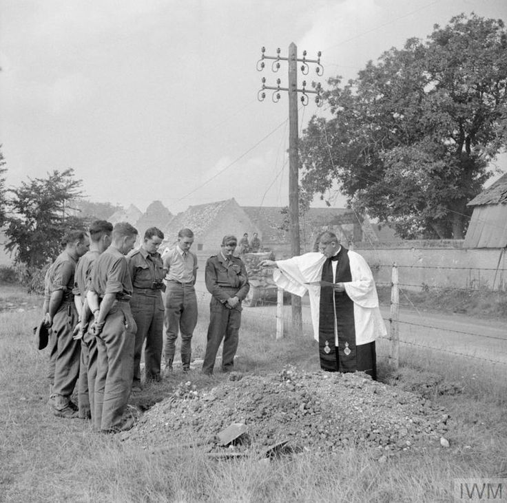 Beside the road to Lesieux in Normandy, France, a British Army Chaplain presides over the burial of a fallen soldier as tanks of the 8th Hussars continue the advance.