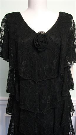 Vintage Dress Lace Black Deadstock Flapper Style NOS .  Original tags as shown on this layered black lace dress.  Rose on the bodice and lace sleeves as shown on this new old stock dress. .  Patra label and original Foleys store price tag of $148.00.  Size 8 on dress label and size 7 to 8 on tags.  Laid flat in inches for measurements.  18.0 Bust.  17.25 Waist.  19.50 Hips.  34.50 Length from back of neckline to hem.  12.50 Sleeve from neckline to hem of sleeve.  Very good to excellent clean…