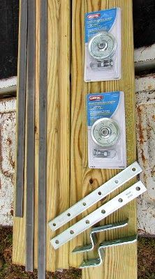 "3, 4 ft. strips of flat bar, .25"" x .75"" 2 garage door pulleys  2 mending plates 2 door stops 1 pressure treated 1x6"