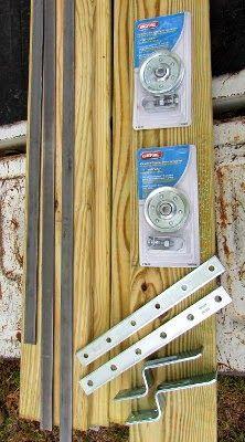 """3, 4 ft. strips of flat bar, .25"""" x .75"""" 2 garage door pulleys  2 mending plates 2 door stops 1 pressure treated 1x6"""
