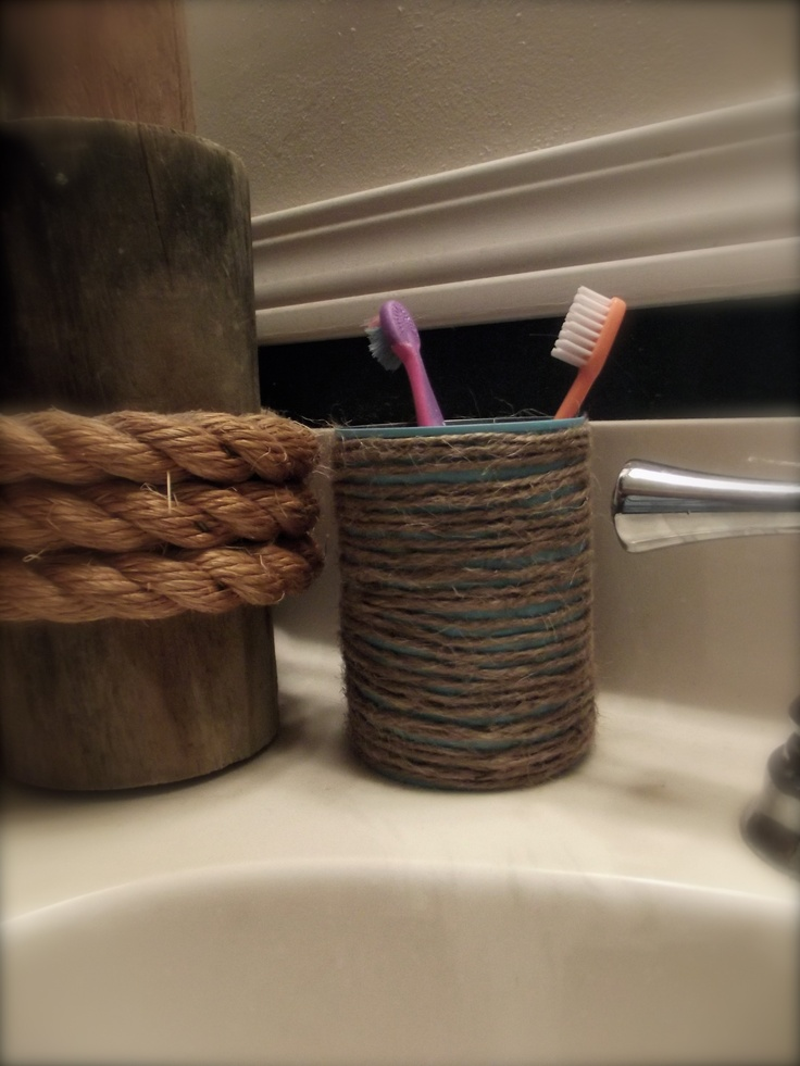Toothbrush holder I made from an empty tin can.  Spray painted it to match my ocean themed bathroom, then hot glued twine around it.