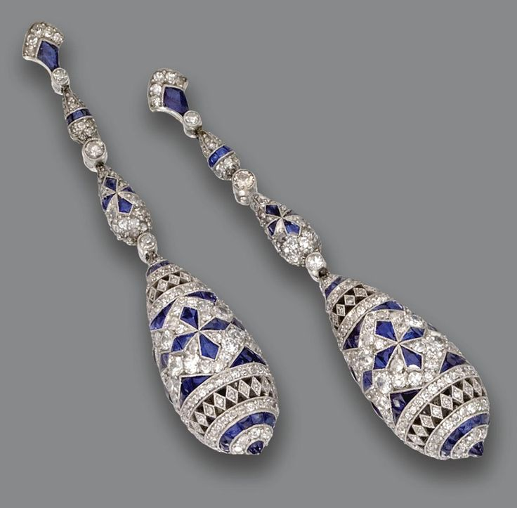 PAIR OF SAPPHIRE AND DIAMOND PENDANT-EARRINGS.  The partly openwork pendants of ovoid form, decorated in a stylized floral pattern with small calibré-cut sapphires and round and single-cut diamonds, suspended from fringes of similarly decorated links, mounted in platinum. Art Deco or Art Deco style.