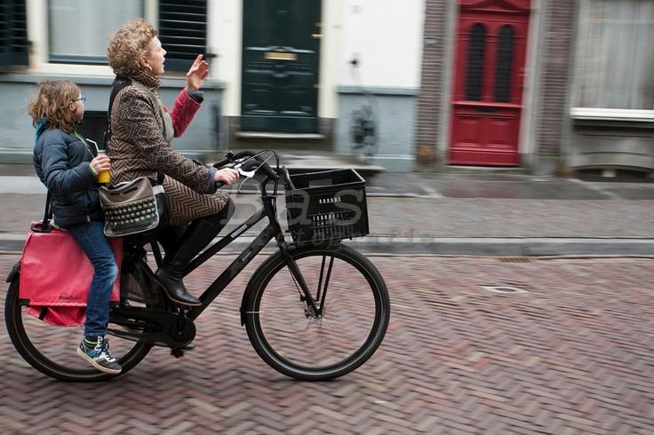 Een moeder fietst met haar kind achterop door Utrecht.