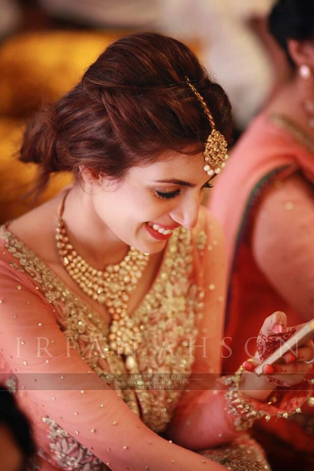 Bride wearing bridal lehenga and jewelry. #BridalHairstyle #BridalMakeup #BridalFashion #BridalPhotoShoot