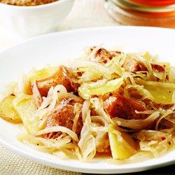 """Here's our weeknight version of choucroute garni, """"dressed sauerkraut,"""" made with chicken sausage. The flavor of the dish will vary depending on what type of chicken sausage you choose. We like the taste of roasted garlic sausage or sweet apple sausage in this recipe. And although any type of sauerkraut can be used, we prefer the crisp texture of refrigerated kraut over canned. Serve with roasted carrots and some mustard to spread on the sausage."""