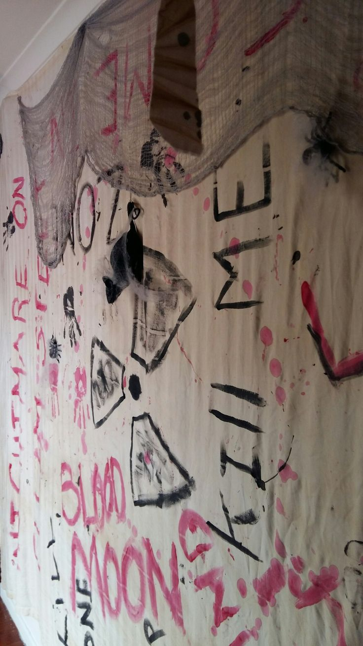decorated the walls with sheets stained in coffee and tea , painted with haunting slogans