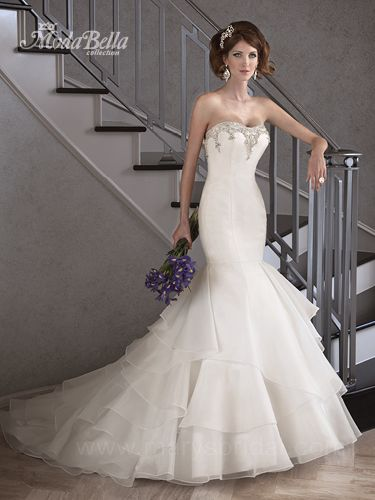 This beautiful organza mermaid gown features a tight fitted bodice and a dramatic ruffle bottom. The intricate beading on the bodice is vintage in every way.