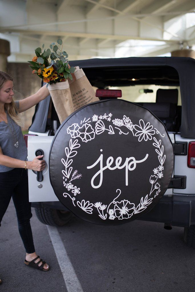 "The original tire cover that started The Tire Cover Shop! A white floral design circling the word ""jeep"" is printed onto a black vinyl tire cover. -Choose from sizes 26""-35"" -Check out our ""how to mea"