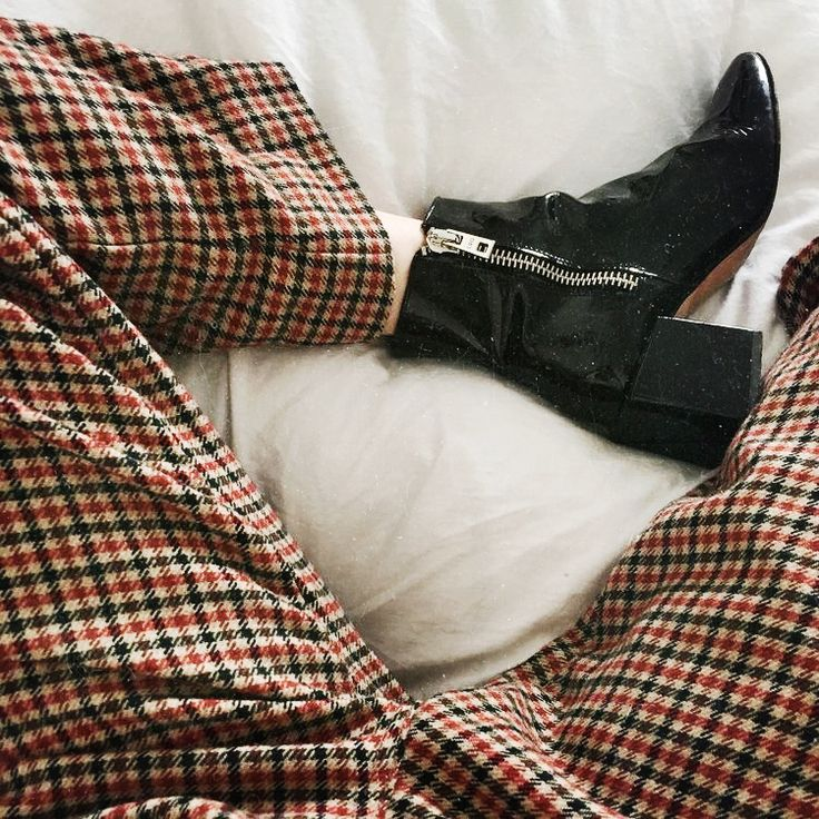 checked trousers and black patent leather boots.
