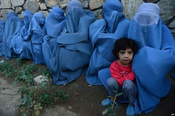 DragonI — tebusa: Afghan women wait with a child to get food...