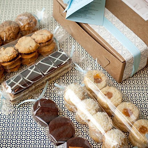 One Girl Cookies' Tea Cookie gift boxes! Hand-tied cellophane sleeves of tea cookies lovingly wrapped in a kraft brown box adorned with a sepia-toned family photo, a decorative logo paper band and cotton twill ribbon in shades of blue and chocolate brown.