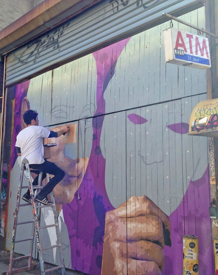 Damien Mitchell at work. Street art work in Brooklyn, New York City. Graffiti is widespread - with many murals, wheatpastes and stencils.