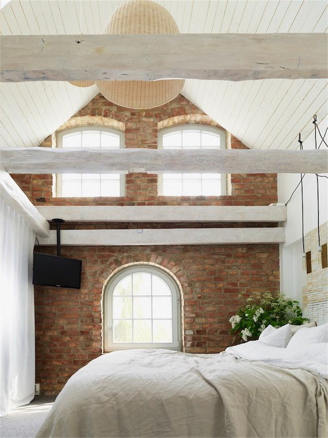 Exposed beams in the bedroom up in the eaves of a Swedish house.