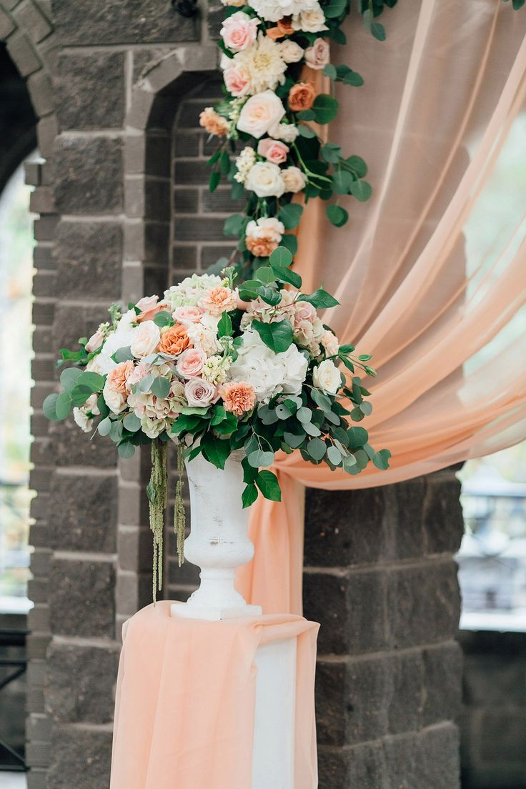 Flower arch with a light peach-colored fabric decorated with compositions in high vases on the sides using roses, carnations, hydrangeas, methiol, eucalyptus and salal