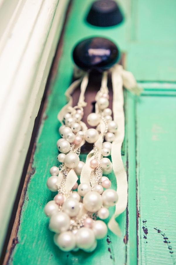 Pearls hanging on a vintage door.