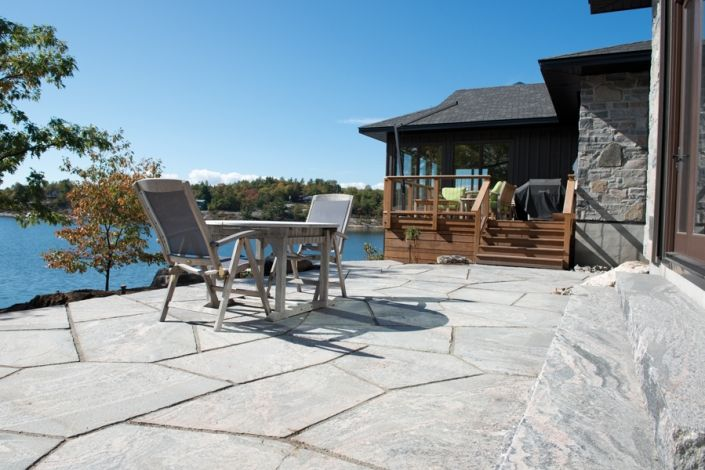 """Just one aspect of a multi phase project on the shores of Georgian Bay,   this formal dining patio was created with 3"""" flagstone from the Muskoka Rock Company's Rosseau Granite Quarry.  The installers cut each joint creating a uniform five point random design. The calibrated thickness and ultra smooth, yet natural, stone finish ensures that guests in even formal footwear are safe and comfortable."""
