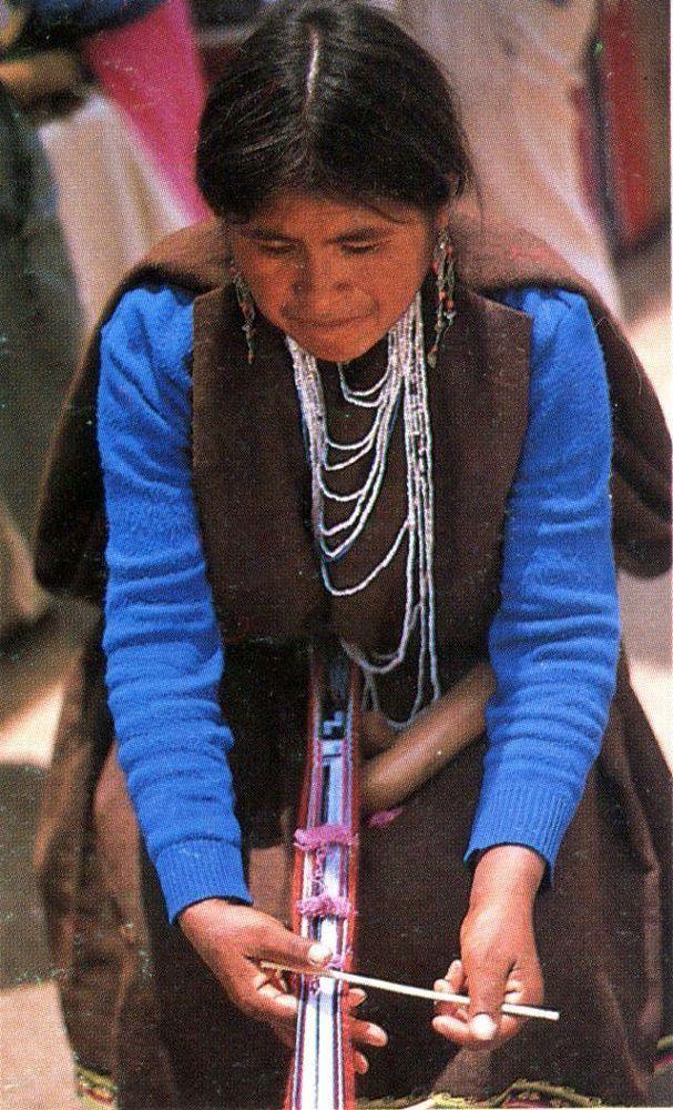 """Mujer teje una faja en un telar de cintura, instrumento típico de la costa andina.  Fotografía Sara Larraín. S/F. En: """"Norte Grande 500 Años Después"""". Sara Larraín Ruiz Tagle. Editorial La Puerta Abierta. 1989."""