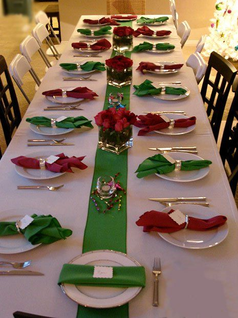 White table cloth with red green napkins place in white plates, long green wide ribbon down center of table with short glass containers holding red flowers, could use floating candles in water.
