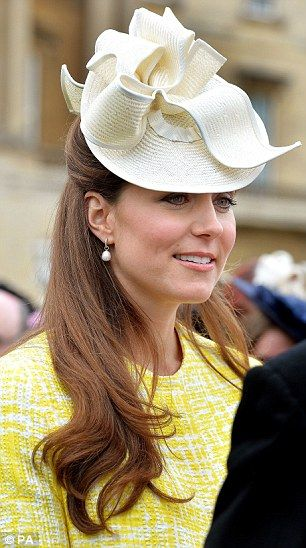 2013: Old favourite: Kate wearing a cream sinemay Jane Corbett hat at the Buckingham Palace garden party