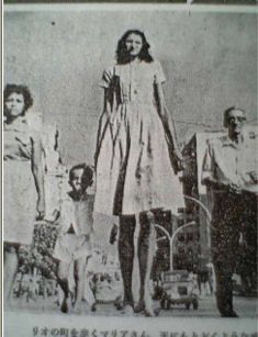 Maria Feliciana dos Santos grew normally until the age of 10, when her growth skyrocketed. She was a basketball player, singer and circus attraction. Her first public performances were in 1962 at the age of 16. At 18 she received the title of Queen of Height in a contest in Chacrinha. Although her height was often claimed to be 7 feet 4.4 inches (224.8 cm), her real height was probably no more than 7 feet 0 inches.