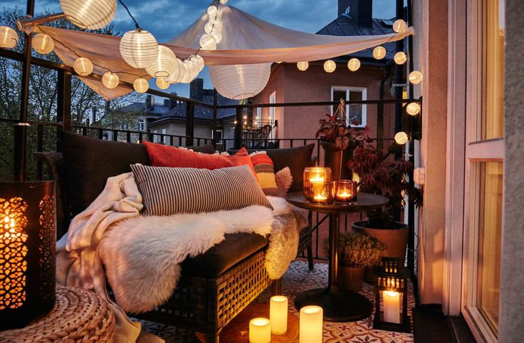 A cozy balcony with lit LED light chains, a canopy, lanterns with lit candles and a sofa filled with cushions and sheepskin rugs.