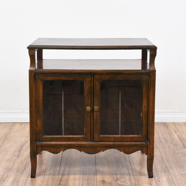 This rustic media cabinet is featured in a solid wood with a raw dark walnut finish. This entertainment center is in good condition with 2 glass display doors, record cabinet storage and carved curved base trim. Perfect for holding a tv or record player! #farmhouse #storage #mediacenter #sandiegovintage #vintagefurniture