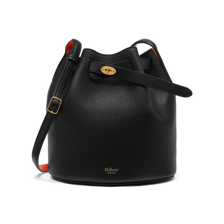 Shop the Abbey in Black & Bright Orange Small Classic Grain Leather at Mulberry.com. The Abbey is a traditional 'bucket bag' with drawstring detailing, contrast lining and a range of eye-catching or iconic leather finishes. The Abbey features the iconic postman's lock as a nod to Mulberry's heritage DNA, securing a simple belt closure on a timeless, easy to wear style.