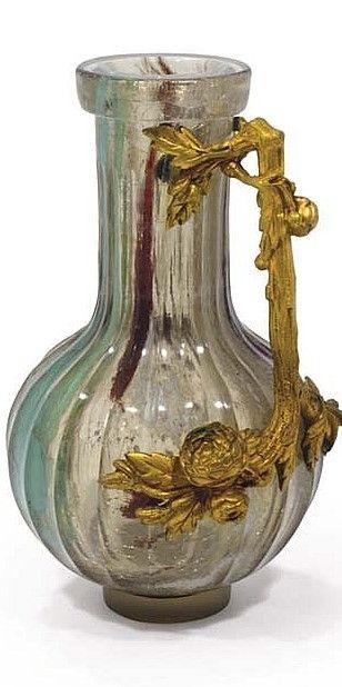 ERNEST-BAPTISTE LEVEILLE (1841-1913) PICHET, VERS 1890 En verre craquelé à salissures intercalaires vertes, prune et blanches, de forme balustre sur talon, le corps cannelé, agrémenté d'une anse en bronze doré simulant un branchage fleuri Hauteur : 21 cm
