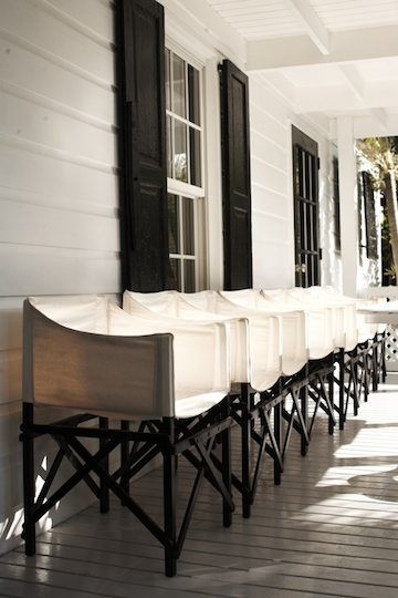 india hicks house on harbor island - white house, black shutters, white chairs with black legs lined up against house on porch