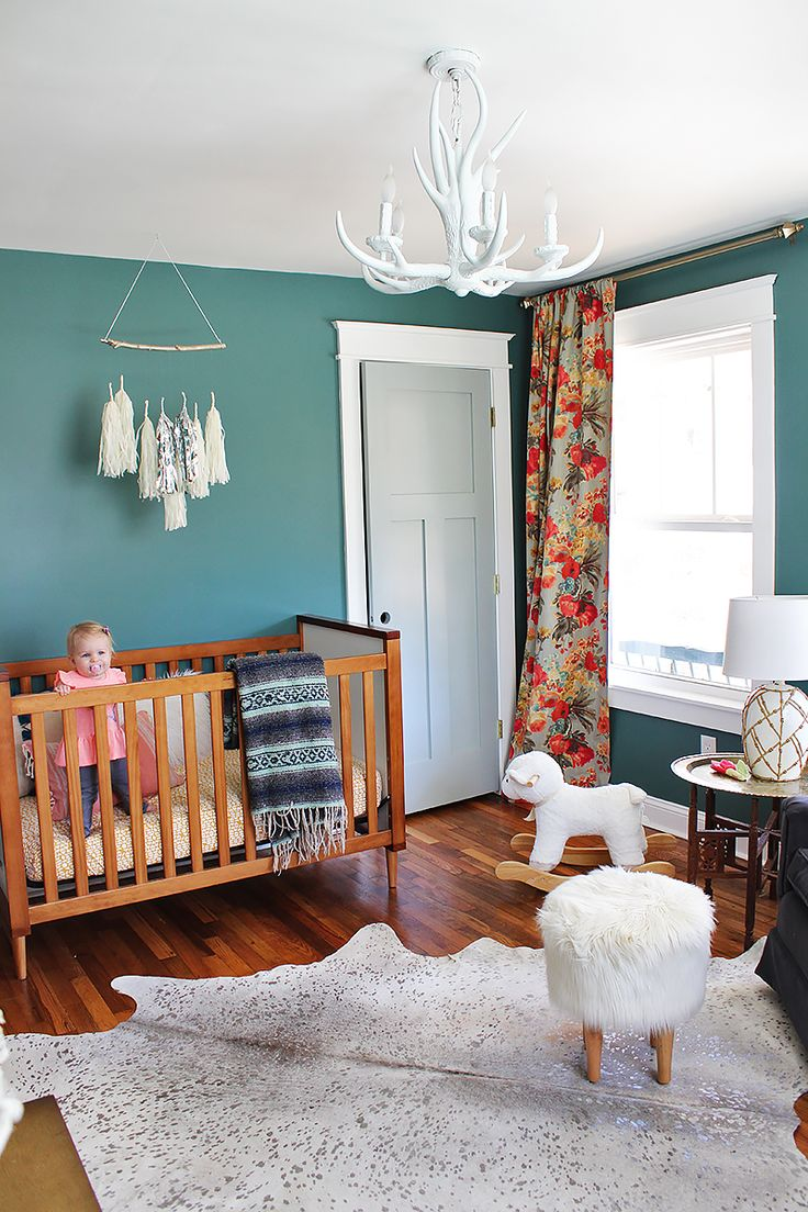 Sweet eclectic & boho nursery for a little girl with white antler chandelier and floral curtains