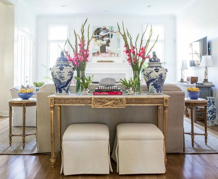 Beautiful transitional living room is fitted with two cream pleated skirted stools positioned beneath a gold sofa table finished with a white marble top topped with blue and white Chinese ginger jars flanking flowers in glass vases and stacked decorative books.