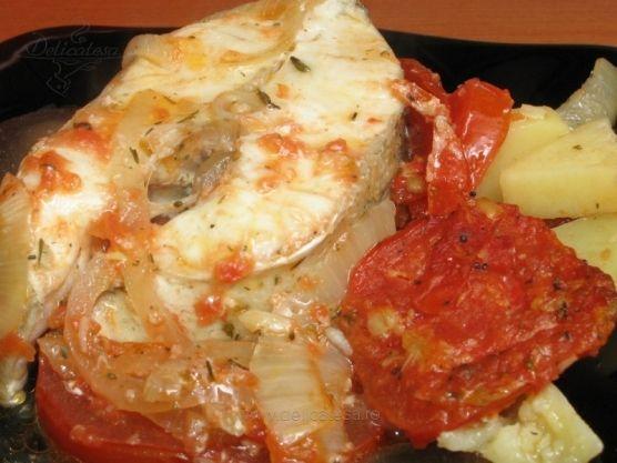 Rondele de şalău preparate la cuptor pe un pat de roşii cu ceapă, cartofi şi cu un sos de roşii, usturoi, vin alb şi cimbru