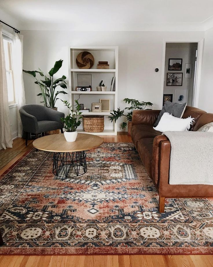 Modernes Vintage Wohnzimmer mit brauner Couch und schwarzem Sessel, großflächigem Teppich