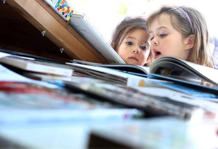 Feria del Libro de Madrid. Dos niñas miran libros en una caseta.