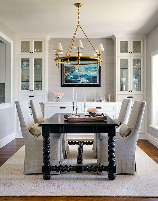 Dining Room With Built In Cabinets And Buffet Dramatic Light Fixture Black Table Gray Slip Covered Chairs
