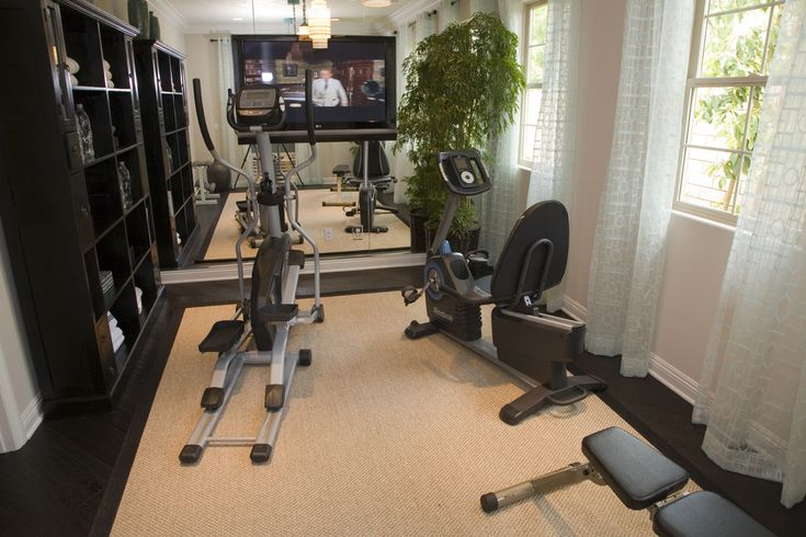 Small room with elliptical trainer and recumbent exercise bike with built-in wood shelving and mounted television screen on the wall