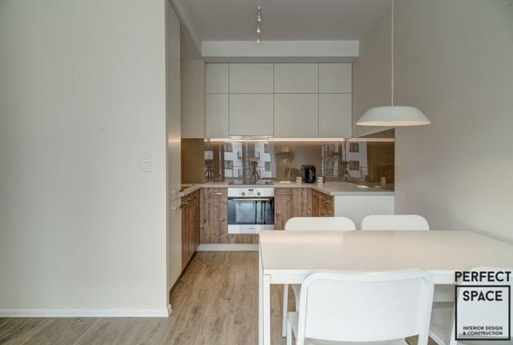 """Kuchnia umieszczona we wnęce, o klasycznym układzie litery """"L"""". Białe fronty szafek idealnie współgrają z motywem drewna na dolnych szafkach i z podłogą."""