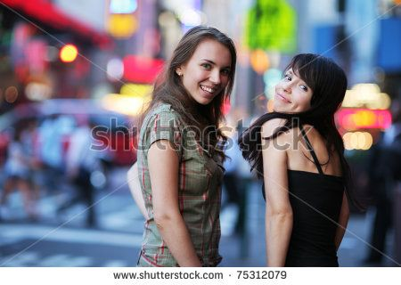 Two beautiful young women at Times Square in New York City. Shallow DOF. - stock photo
