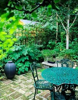 Brick paved small courtyard garden with green metal table and chairs