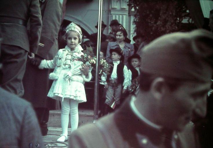 Magyar tisztek társaságában díszmagyarban várja a kormányzót egy szép magyar kisleány.