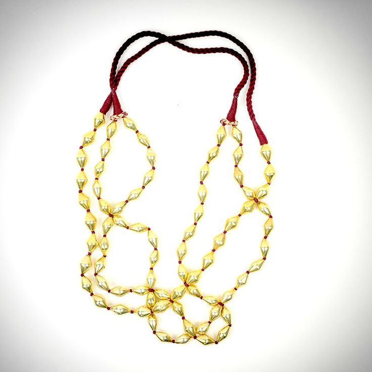 AMRAPALI  Jaipur    Gold plated silver dholki shaped beads strung on a red cotton thread