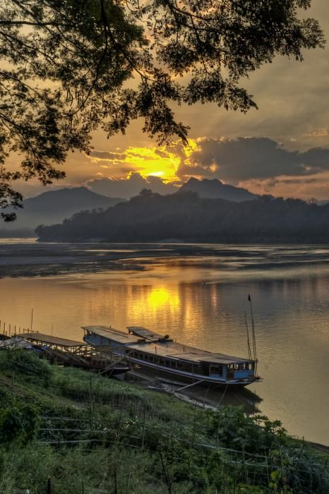 ✮ Sunset over the Mekong River with Laotian junk in foreground in Luang Prabang, Laos