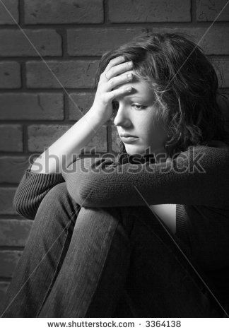 Teenage girl siiting against brick wall in a depressed state