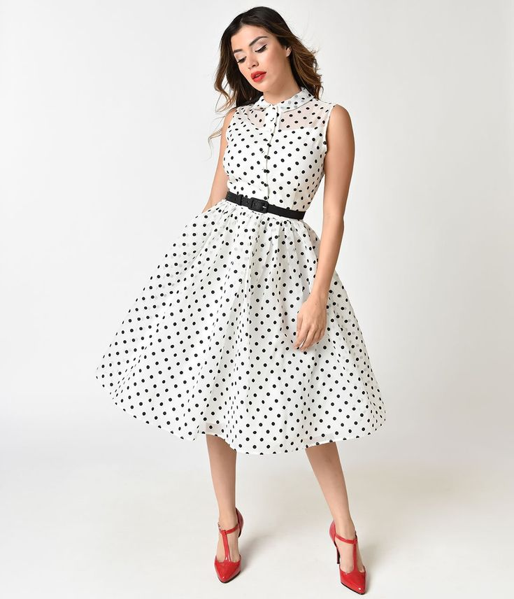 Raise your standards, dolls! An adventurous infused stunner from Unique Vintage, the Georgia Swing Dress is a gorgeous 1950s inspired frock for a vintage peach! Covered in a fabulous array of black polka dots and crafted in a gauzy layer of radiant white poly organza resting over shiny white lining for a marvelous peek-a-boo effect. A sleeveless button up bodice boasts darted seaming that ends at the natural waist, where a fluid skirt billows past knee length and a black adjustable belt nips…