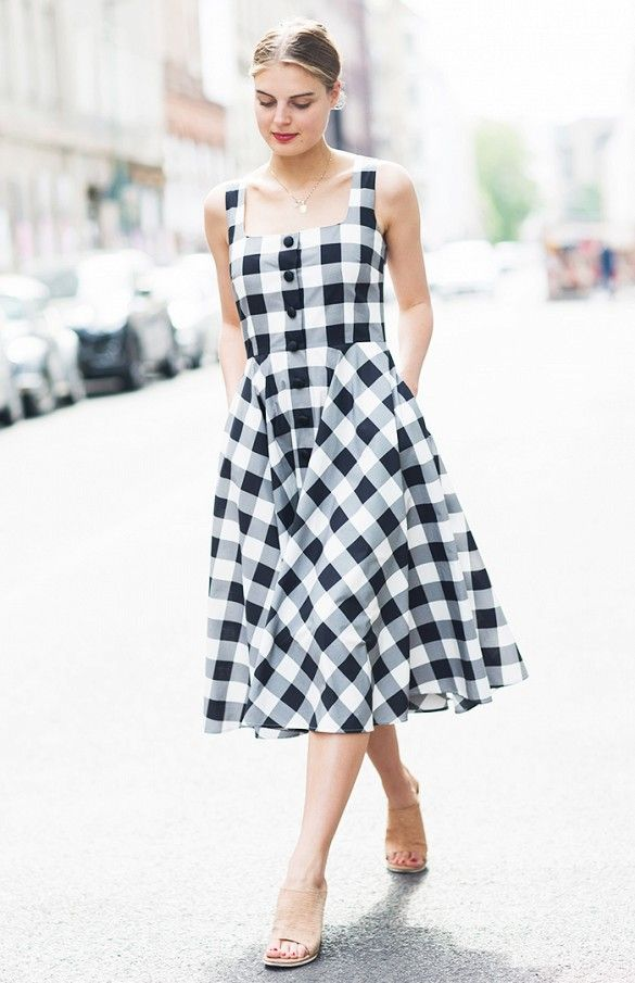 A feminine gingham midi dress is worn with nude mules
