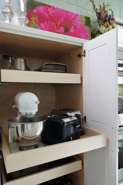 The demicabinet is used to display art and fresh flowers on top, but open the doors and you'll find pullout shelves and electric outlets, so the homeowners can access their appliances without bending and lifting, and in some cases without having to take them out and set them on the counter.